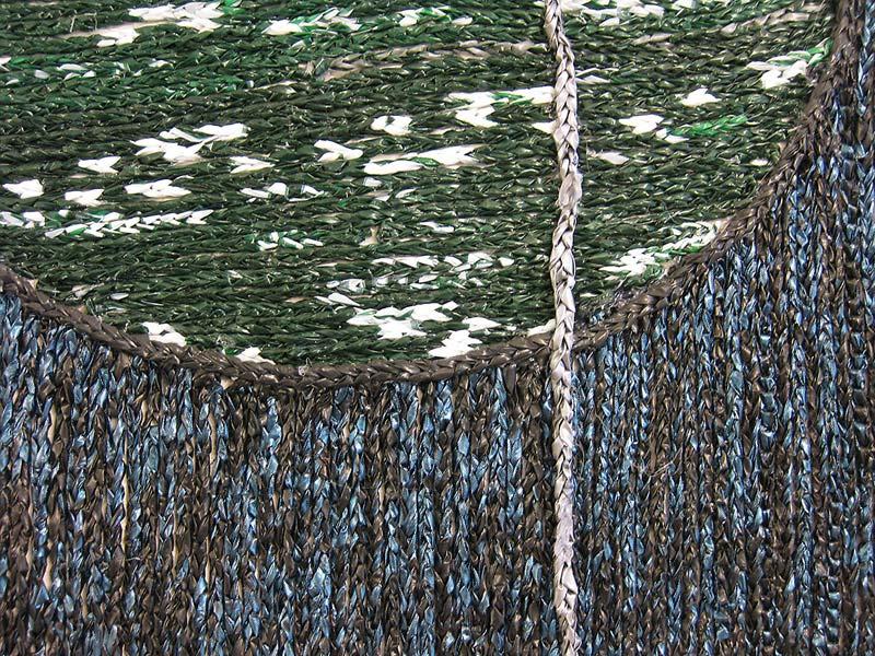 geflochtene Schnüre aneinander gelegt, in grün, weiß, blau und schwarz.