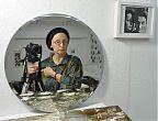 Rita Ostrowskaja mit Blick im runden Spiegel, neben ihr der Fotoapparat.